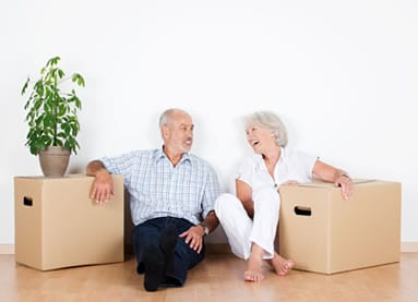 Elderly couple sat on the floor laughing with storage boxes