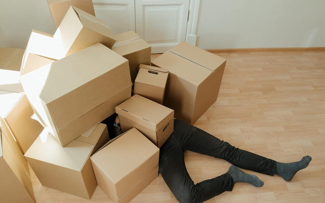 A man on the floor covered with fallen storage boxes