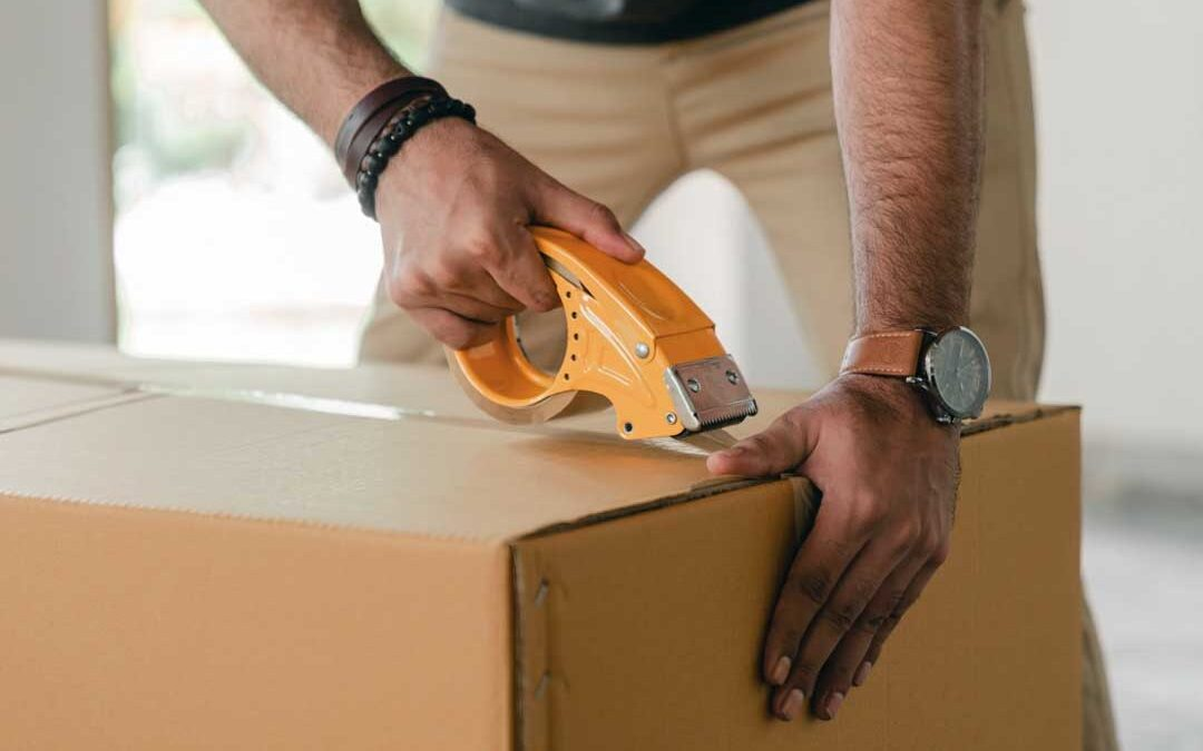 A man taping up a storage box